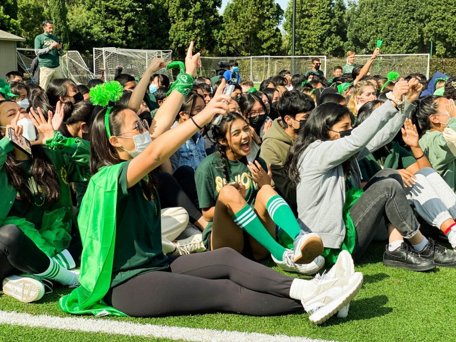 High school students sitting on a football field and dressed in green cheer and raise thier pointer fingers in a #1 gesture.